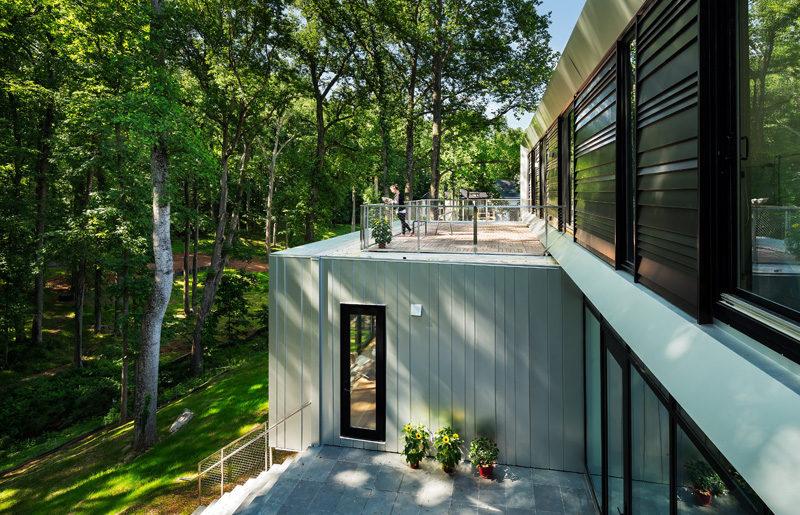 The upstairs of this modern house has access to a small outdoor area that sits on the roof of the lower floor of the home. #OutdoorArea