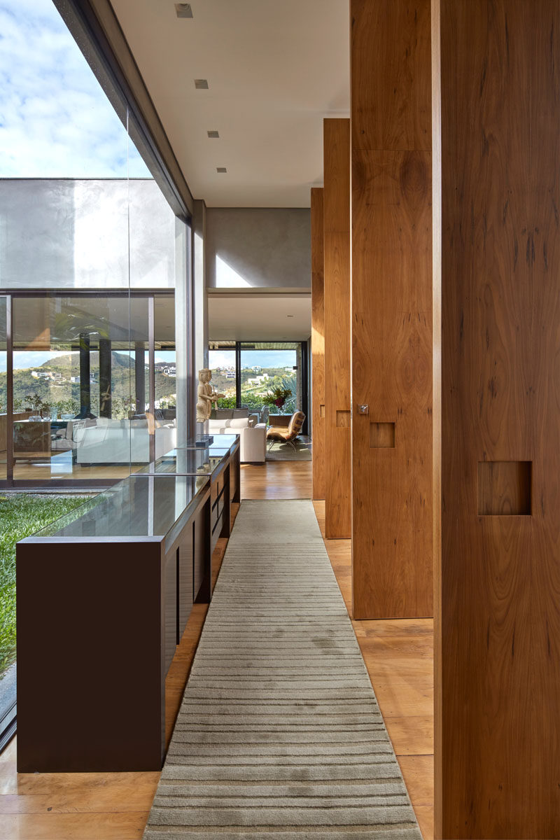 Stepping inside this modern house, large windows surround an internal garden, while a hallway leads to the main living areas of the home. #Windows #Hallway