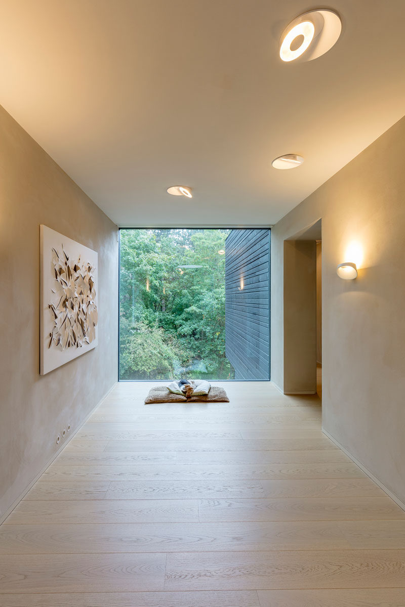 A large picture window at the end of this hallway provides the perfect place to sit on come cushions and watch nature. #Windows #Hallway