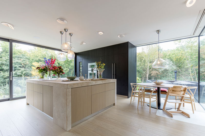 In this modern kitchen and dining room, a black box in the corner houses the ovens, fridge and storage cabinets, while the large island provides plenty of counter space. Next to the kitchen is a space dedicated to the dining table. #ModernKitchen #RoudDiningTable