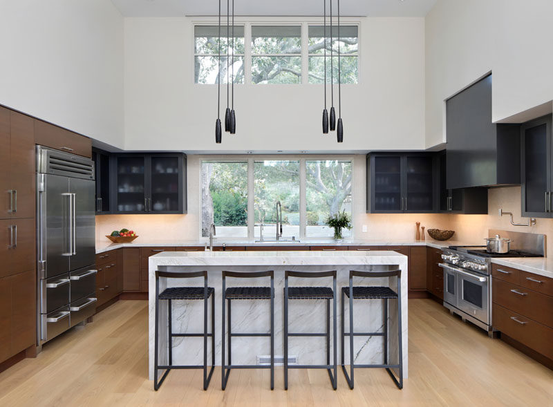 In this modern kitchen, the palette reflects the colors and materials used on the exterior of the house. Marble countertops are paired with stained base cabinets that match the exterior wood siding of the house, while a dark grey hood and upper cabinets match the exterior metal elements. #ModernKitchen #KitchenDesign