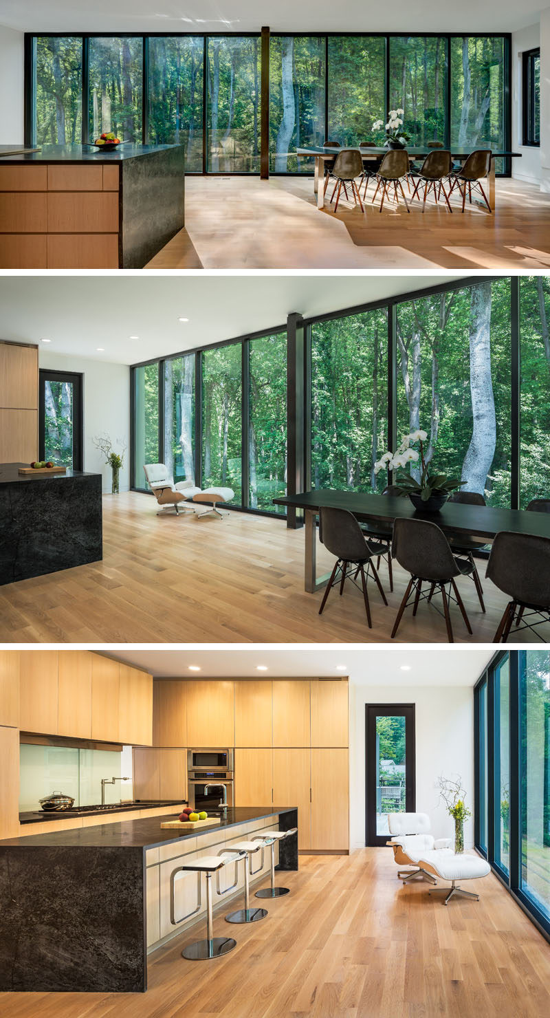 A wall of windows creates a natural backdrop for this large multi-use room. In the kitchen, light wood cabinets have been contemporary with dark stone countertops for a contemporary look. #Kitchen #KitchenDesign #DiningRoom