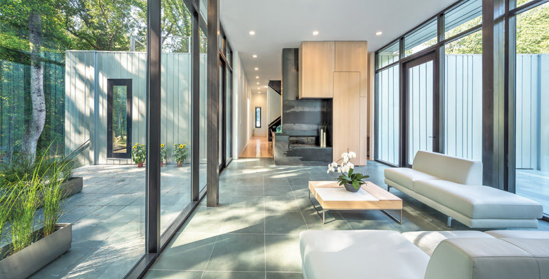 Inside this modern house, there's a sitting area with a hot-rolled steel fireplace. #SittingRoom #Fireplace