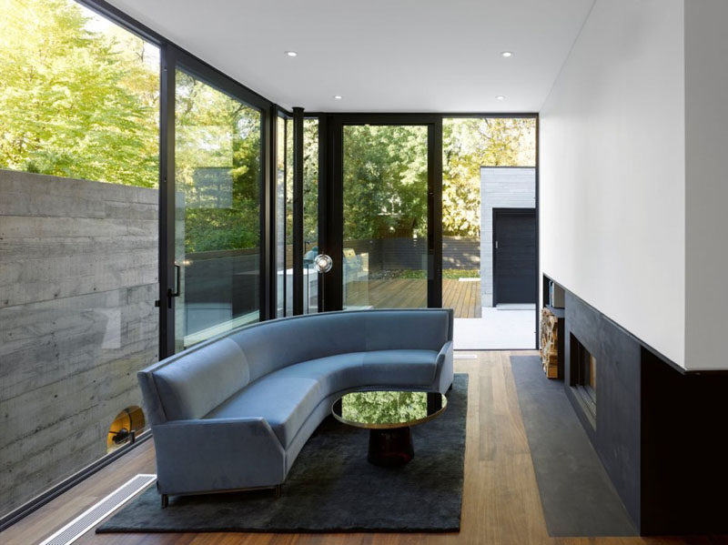 Floor-to-ceiling windows allow plenty of natural light into this modern living room, and a fireplace keeps the space warm on a cool night. A door provides direct access to the patio and backyard. #LivingRoom #Fireplace #Windows