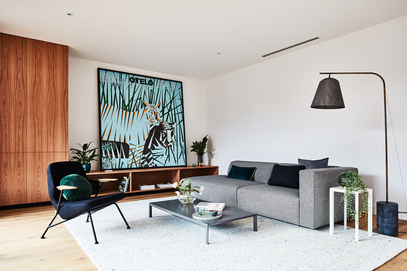 This modern living room has a large piece of artwork draws the eye and adds a pop of color to the room. #ModernLivingRoom #InteriorDesign