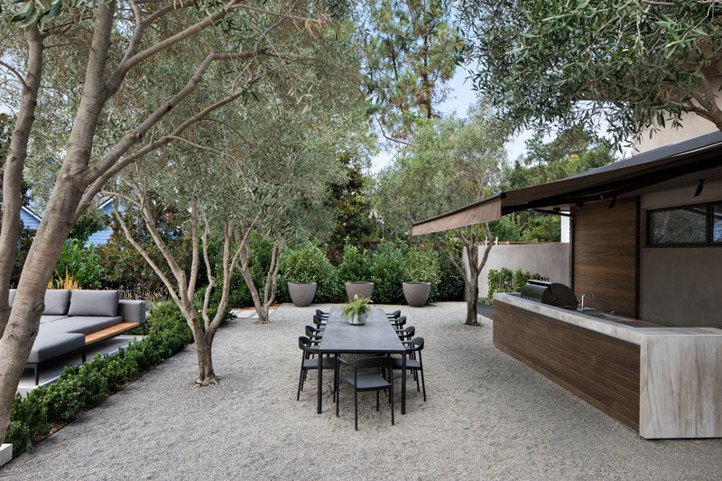 This outdoor kitchen and dining area looks out to the pool, and sits among a grove of olive trees. #OutdoorKitchen #AlfrescoDining #Landscaping