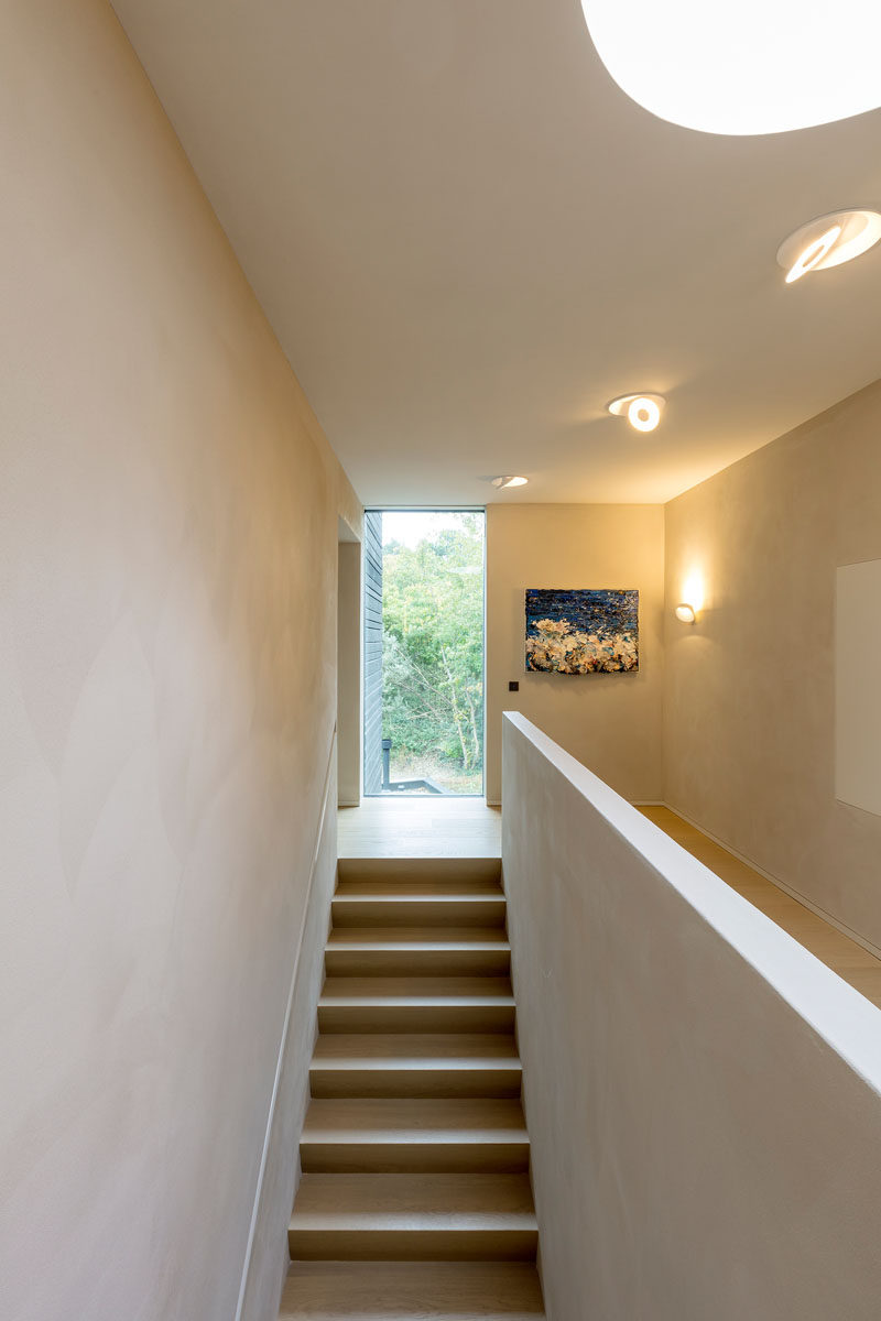 Simple stairs lead to the upper floor of this modern house. #Stairs #Window #Hallway