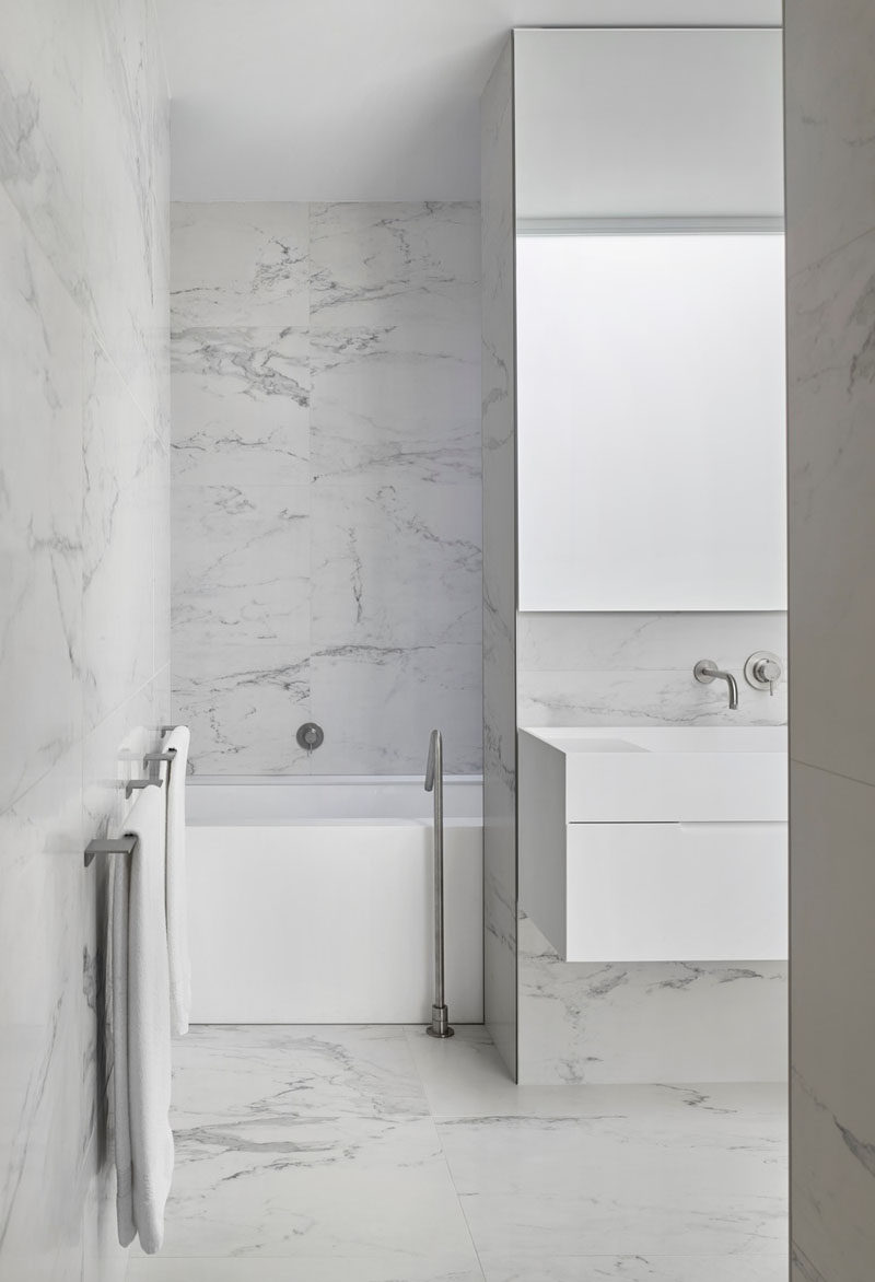 In this modern bathroom, grey stone tiles are combined with a minimalist white vanity and bathtub to create a contemporary look. #ModernBathroom #BathroomDesign