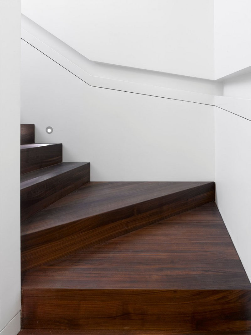 This modern house has wood stairs surrounded by white walls that lead up to the upper floor of the home. Built-in handrails create a simple and minimalist look for the stairwell. #WoodStairs #BuiltInHandrail