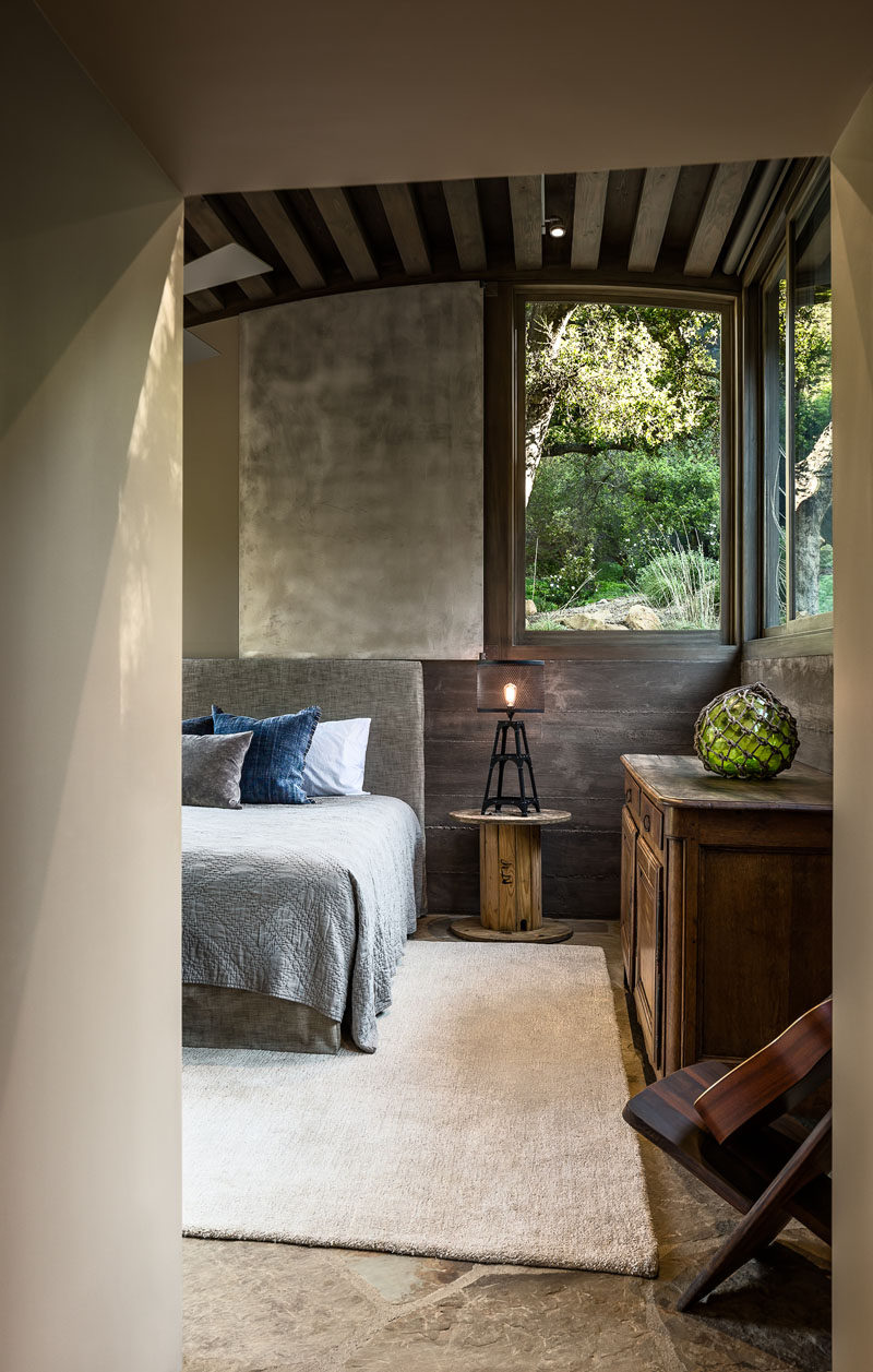 In this rustic modern guest bedroom, stained douglas fir beams have been used for the curved ceiling, while the walls are a combination of colored plaster and board-formed concrete. #GuestBedroom #CurvedCeiling #BoardFormedConcrete