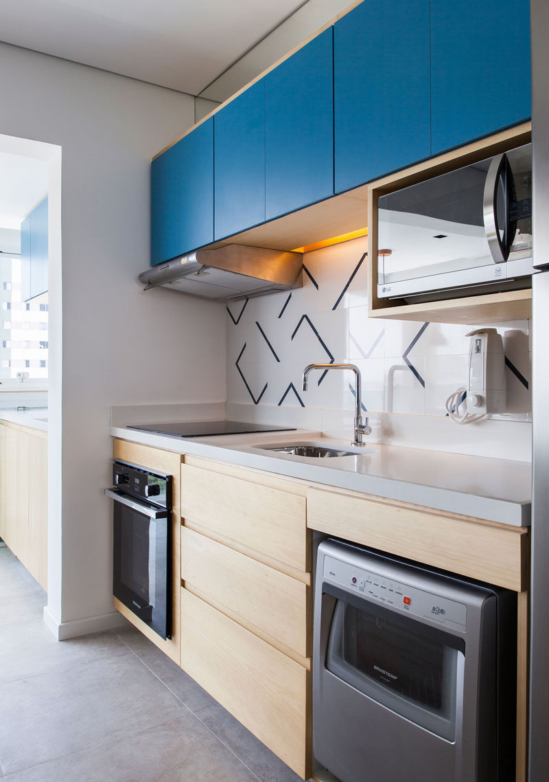 In this small and modern kitchen, bright blue cabinet fronts add a pop of color to the wood cabinetry. #SmallKitchen #KitchenDesign