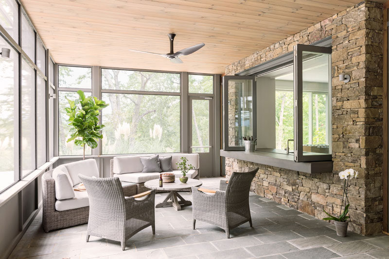 This screened-in porch is a relaxing spot with a couple of curved couches and views of the surrounding landscape. #Porch #EntertainingSpace