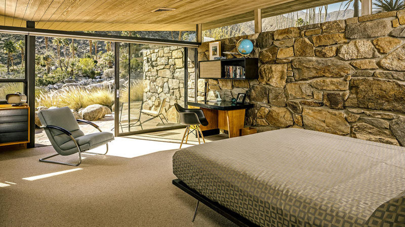 In this mid-century modern bedroom, there's a stone wall that flows from the interior through to the exterior, while a large sliding glass door provides access to a private patio. #StoneWall #Bedroom #MidCenturyModern