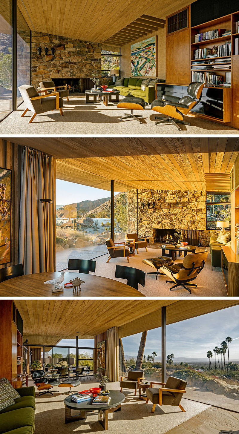 This mid-century modern house has an open floor plan with a sloped ceiling, a stone wall with fireplace, and large floor-to-ceiling windows. Wood elements like a bookcase and the ceiling are also included.#MidCenturyModern #InteriorDesign #Fireplace #StoneWall