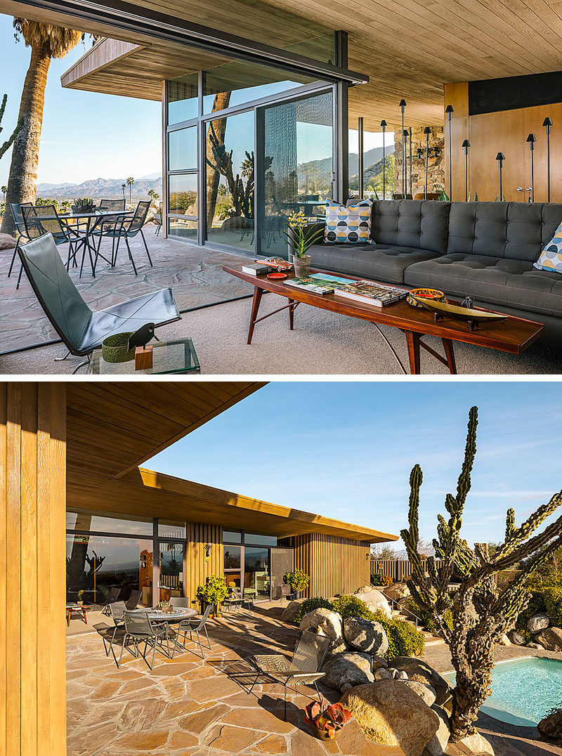 This mid-century modern house has sliding glass walls that open up a second living area to a flagstone patio outside. #MidCenturyModern #InteriorDesign #Patio