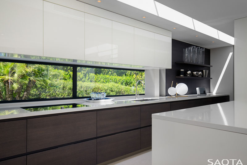 In this kitchen, hardware-free white upper cabinets have been paired with wood lower cabinets and open shelving for a minimalist look. #MinimalistKitchen #KitchenDesign