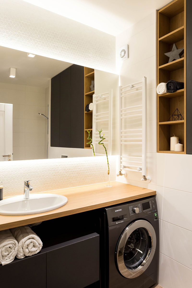 This modern bathroom has a cabinet on the wall creates plenty of storage, while wood lined open shelving is the perfect place to display some simple decor. A backlit mirror provides ambient lighting to the space. #ModernBathroom #BacklitMirror