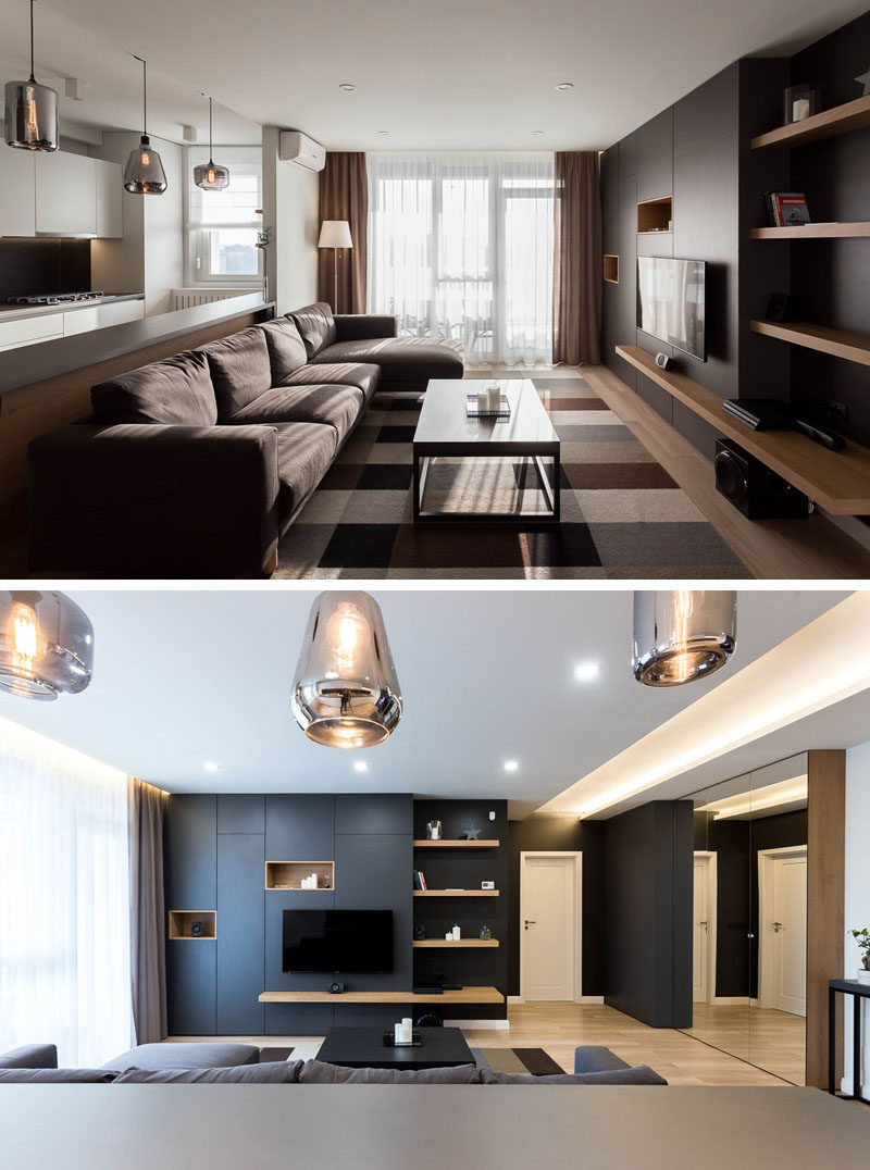 Throughout this modern apartment, like in the living room, the designers worked with a simple color palette of white, grey and black, with touches of brown and wood to help create a warm atmosphere. #ModernApartment #LivingRoom #WoodShelving