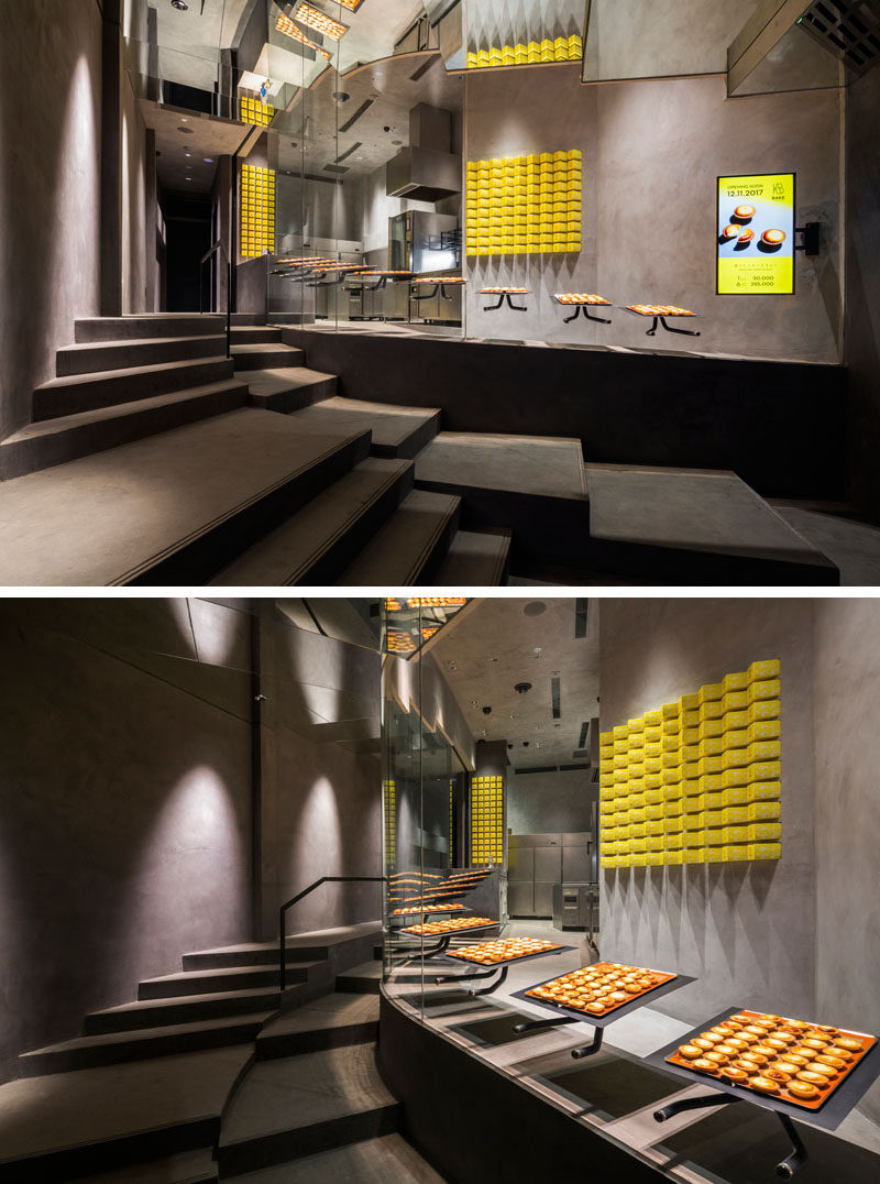 To create a unique look, the stairs that lead from the entrance of this modern bakery to the cashier are designed to reflect the slop of the interior of the store, allowing people walking past or queuing to see the workers inside. #ModernBakery #RetailDesign #StoreDesign