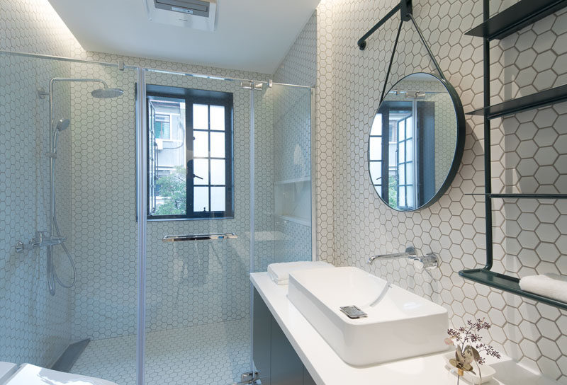 In this modern bathroom, white hexagonal tiles have been used to keep it bright, while black accents create contrast. #WhiteBathroom #ModernBathroom