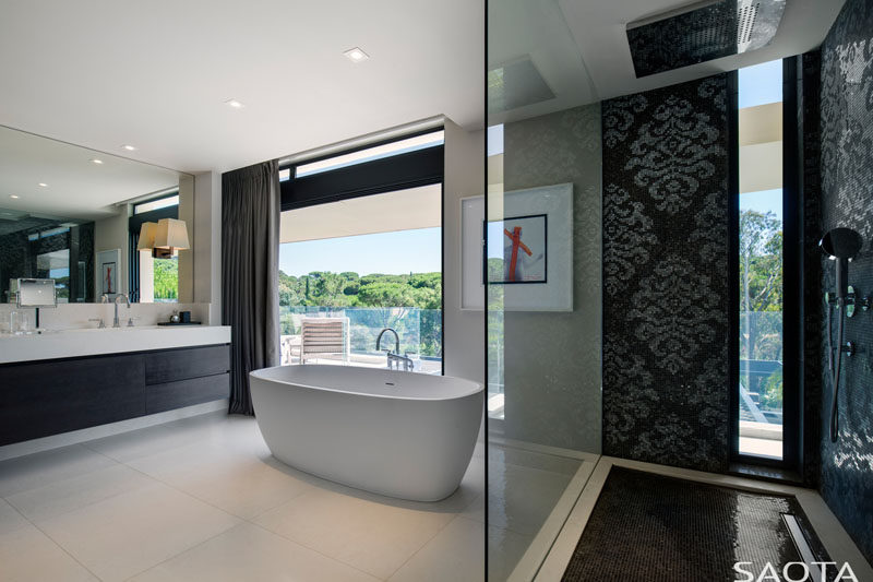 Decorative black tiles have been used in the shower of this bathroom, while a white standalone bathtub is positioned to take in tree views. The vanity combines both black cabinets and a white countertop to complement the overall contemporary look. #ModernBathroom #BlackAndWhite