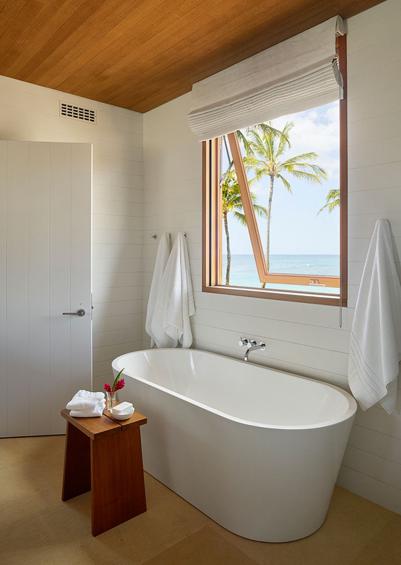 In this modern beach house bathroom, a freestanding white bathtub sits underneath a window with views of the beach. #ModernBathroom #WhiteAndWood