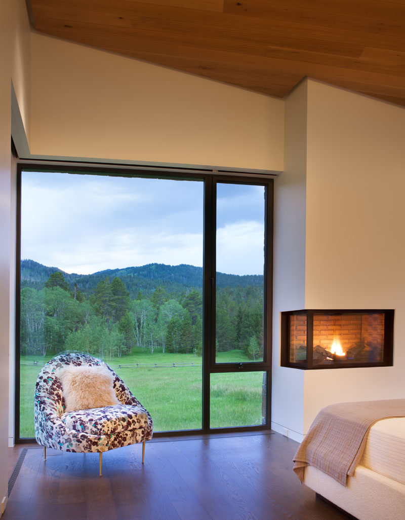 This modern bedroom has a built-in fireplace and a large window to let in plenty of natural light. #Fireplace #Windows