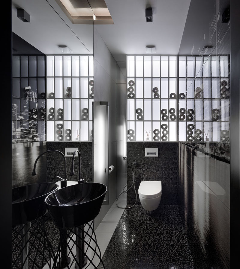 In this bathroom, black tiles and a black sink contrast the white shelving to create a modern appearance. #BlackAndWhite #ModernBathroom
