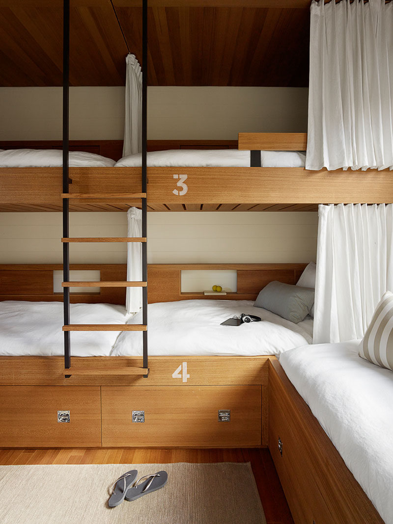 In this modern bedroom, custom bunk beds have been built into the room to maximize the number of beds available. #BunkBeds #BedroomDesign