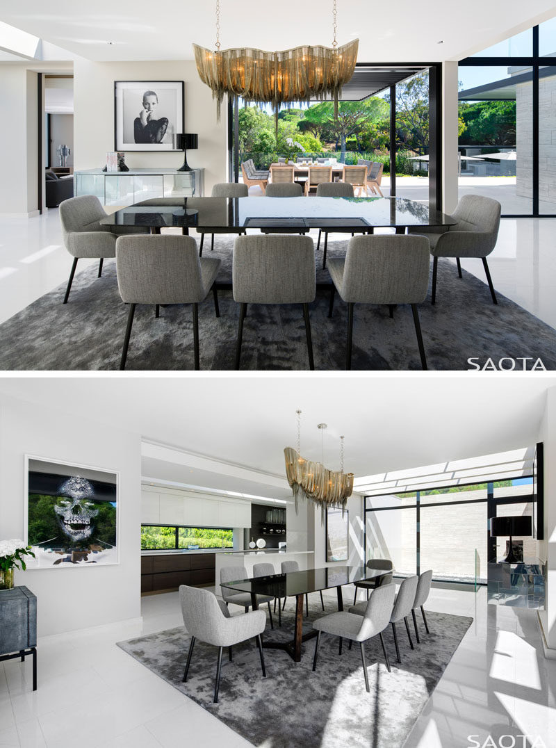 In this modern dining room, a bespoke chandelier hangs over the dining table and adds a touch of luxury to the space, while light vein cut travertine floors contrast the black slim line sliding doors. #DiningRoom #Flooring