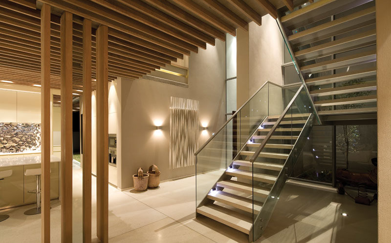 Inside this modern house, there's a double-volume entry hallway and aligned timber slat clad ceilings drawing the eye to the seascape ahead. #Entryway #Stairs