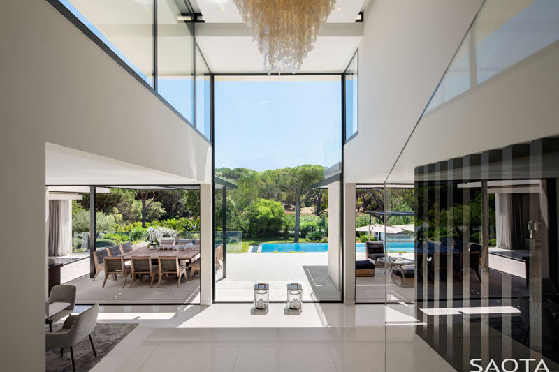 Stepping inside this modern house, there's a capiz shell chandelier occupies the double volume entrance hall area and large frameless windows allow for views over the pool and garden area. #InteriorDesign #Windows