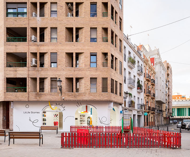 """Creative firm CLAP Studio have designed """"Little Stories"""", a modern children's shoe store in Valencia, Spain, that stands out on the street with its bright white facade and interior. #RetailStore #WhiteFacade #StoreDesign"""