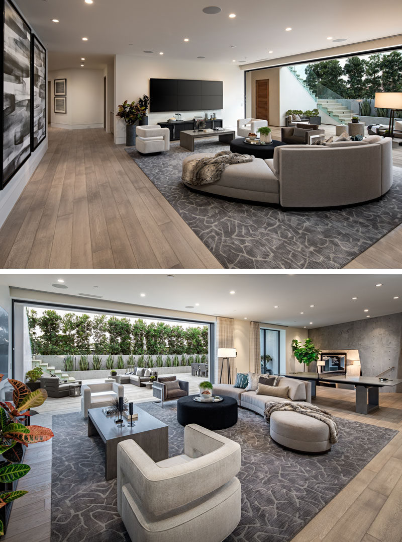 This modern living room has a large curved couch that's focused on the large six screen television setup on the wall. #ModernLivingRoom #InteriorDesign