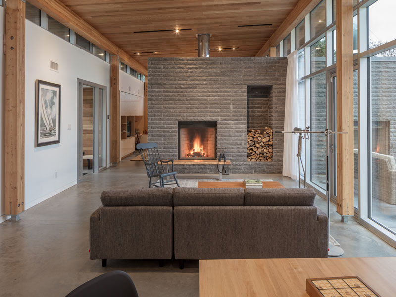 In the living room of this modern house, a stone fireplace surround has been built to accommodate firewood storage. #Fireplace #WoodStorage
