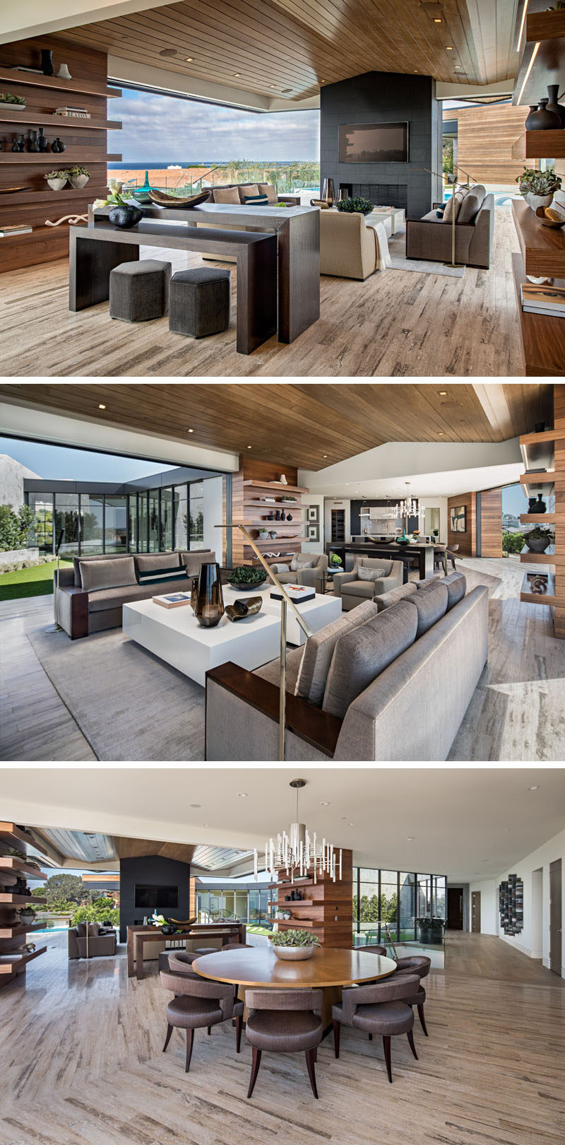 The main living area of this modern house is almost completely open to the outdoors. The living room, with a wood ceiling, is focused on the fireplace and the view, while the circular dining table separates the living room from the kitchen. #ModernLivingRoom #DiningRoom #InteriorDesign