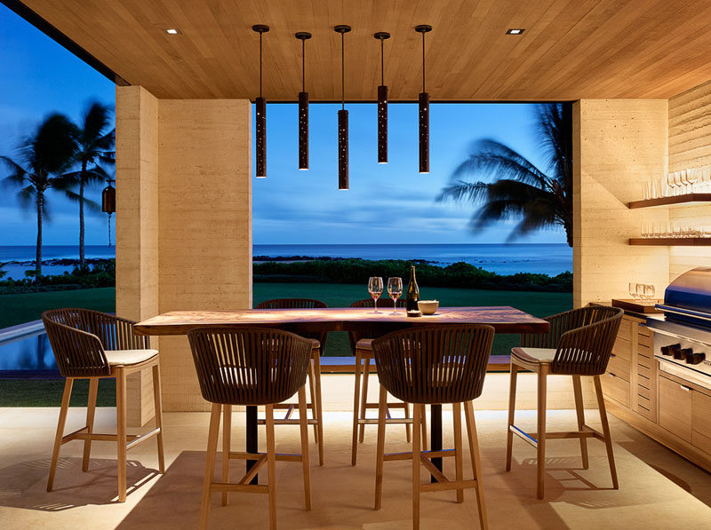 This modern beach house has a covered outdoor kitchen with a barbecue and an alfresco dining area.