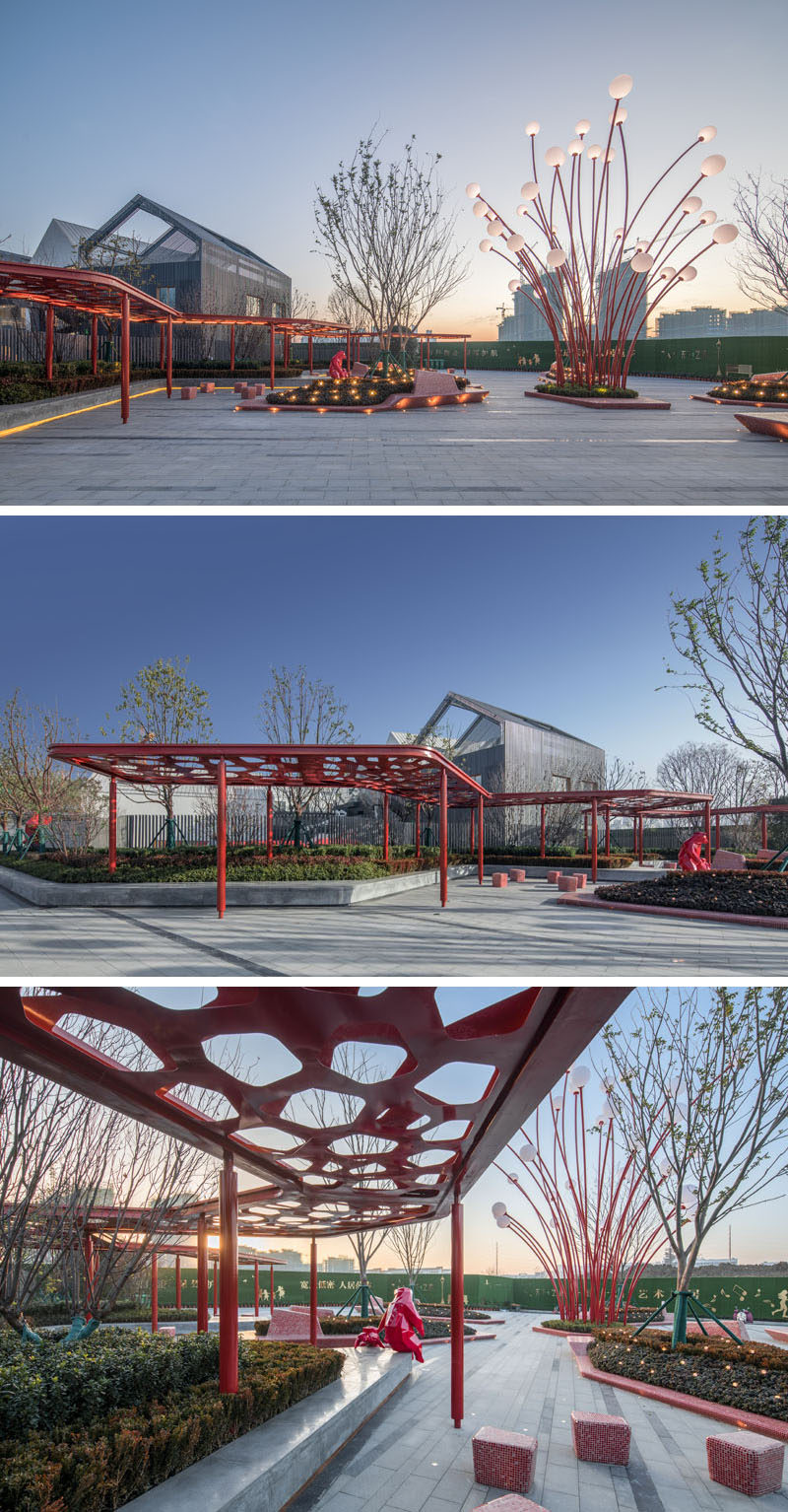 This modern public plaza has a variety of seating options, like a built-in concrete bench that sits underneath a red pergola and that wraps around the planters. #Park #Plaza #LandscapeDesign