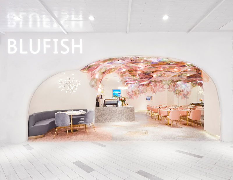 This modern restaurant features hand drawn sea life shapes that were then cut out of colored metal mesh and attached to the ceiling to create a sense of being underwater. #ModernRestaurant #RestaurantDesign