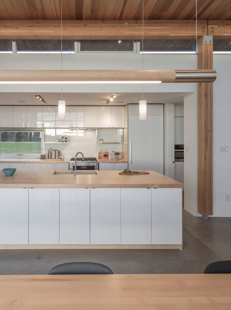 In this modern kitchen, minimalist white cabinets have been paired with wood counters to create a contemporary appearance. #ModernKitchen #WhiteAndWoodKitchen