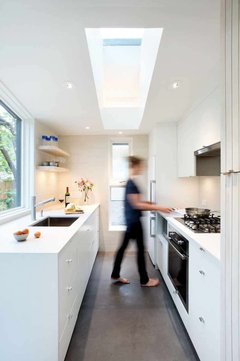 This small kitchen has white cabinets and plenty of windows to allow natural light to brighten the space and make it feel larger. #SmallKitchen #WhiteKitchen #Skylight