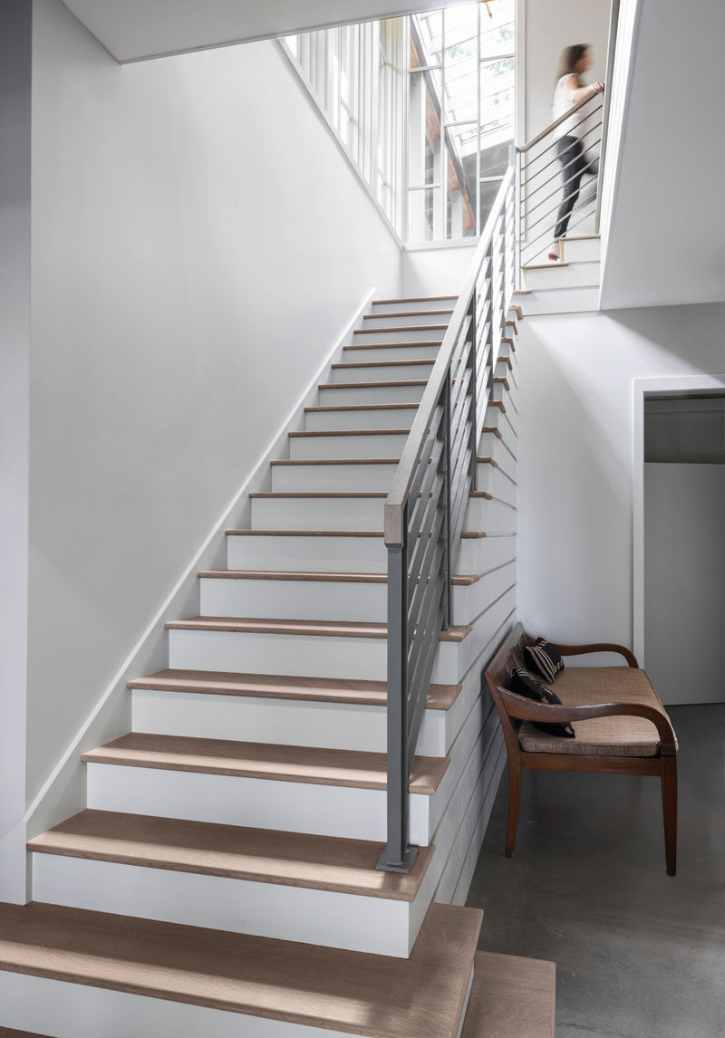 Wood and white stairs lead to the upper floor of this modern farmhouse. #Stairs #InteriorDesign