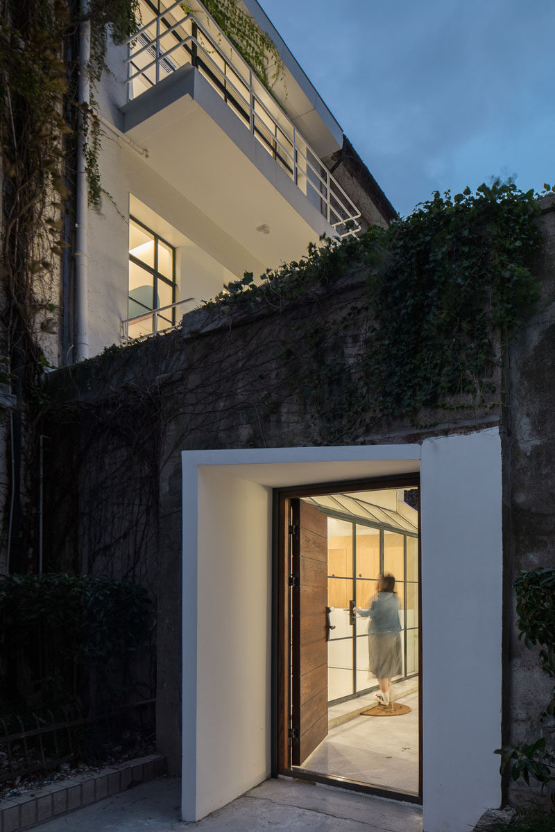 The white entryway and wood door of this modern house stand out against its concrete and vine surroundings. #ModernHouseEntry #FrontDoor