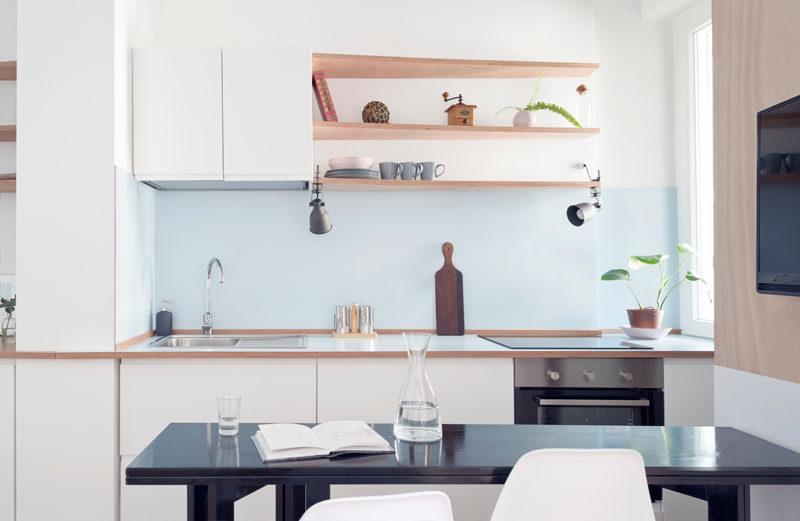 this small apartment kitchen has a light blue backsplash and white cabinets to keep it bright. #KitchenDesign #SmallKitchen