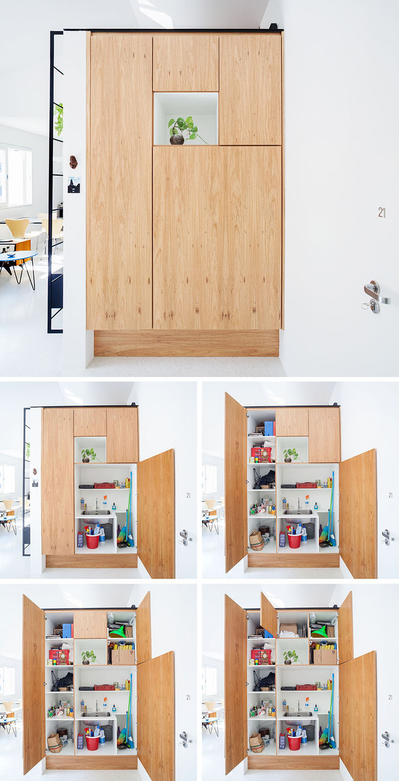 Stepping inside this apartment, you are greeted by a small white alcove with a plant that's surrounded by wood panels. Inside the panels are a variety of shelves and a small sink. #Shelving #Storage #Cabinet