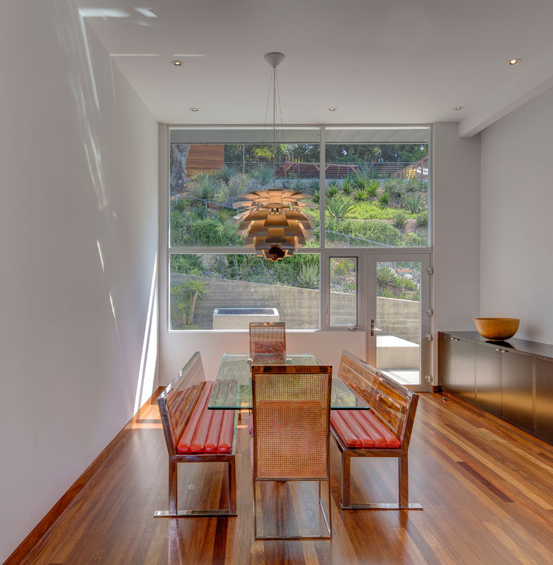 This contemporary dining room is furnished with a glass dining table and bench seating, while large windows provide a view of the landscaped backyard. #DiningRoom #Windows
