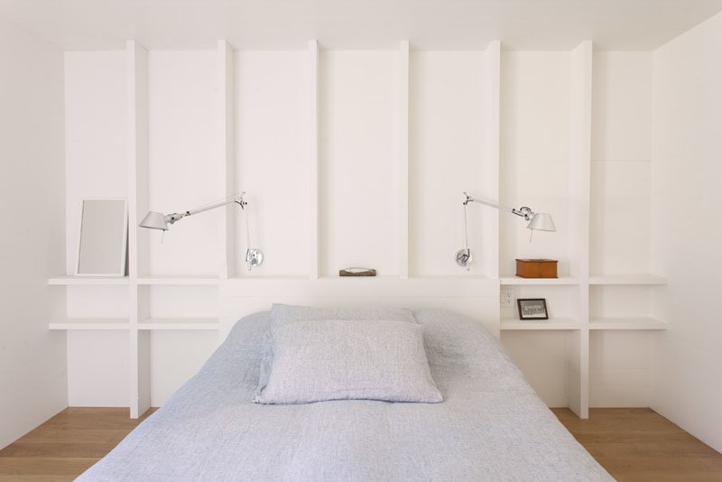 In this simple bedroom, exposed wooden studs have been painted white and act at shelving. #Shelving #BedroomDesign