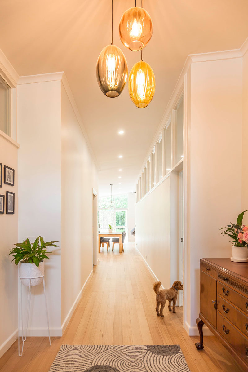 The entryway to this renovated mid-century modern home has three simple colored glass pendant lights. #Entryway #Hallway