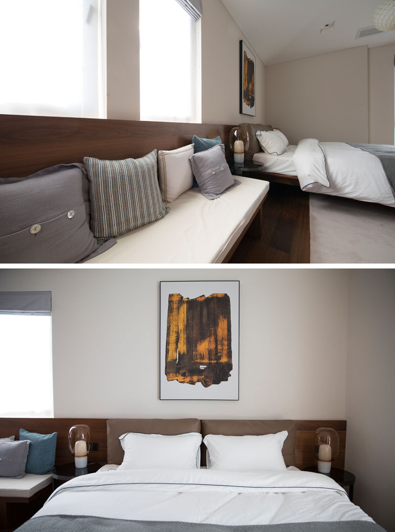 In this modern bedroom, there's a built-in wood bench with an upholstered cushion and decorative pillows. The backrest of the bench transforms into the headboard for the bed, creating a single cohesive look that runs the length of the bedroom, from one wall to the other. #ModernBedroom #BuiltInBench