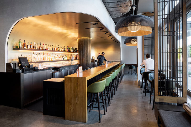 The bar in this modern restaurant appears to be set into a curved niche, that's been finished with silver leaf squares, creating a luxurious, subtly reflective backdrop. #ModernBar #RestaurantDesign